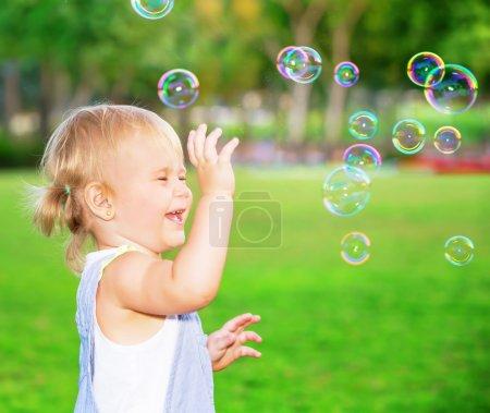 Photo pour Joyeux enfant qui s'amuse dans le parc, jolie petite fille blonde jouant avec des bulles de savon sur la cour, joyeux petit enfant appréciant le jeu en plein air - image libre de droit