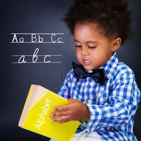 Photo for Little boy on language lesson, holding in hands alphabet, learning letters and spelling, preparing to go to first class - Royalty Free Image