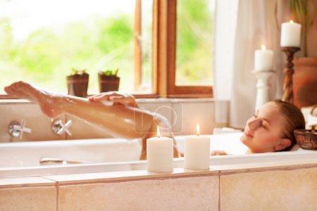 Photo pour Photo de mise au point douce de la jeune femme douce couchée dans la baignoire avec mousse et bougie, profiter de la procédure de spa dans le resor de luxe - image libre de droit