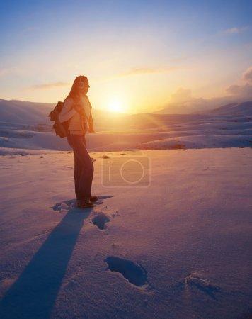 Photo pour Femme voyageuse dans les hautes montagnes enneigées profitant d'un coucher de soleil magnifique, vacances d'hiver actives, mode de vie sain et sportif - image libre de droit