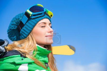 Photo pour Portrait de jolie femelle aux yeux fermés profitant de la nature hivernale sur fond de ciel bleu, relaxant sur la station de ski - image libre de droit