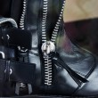 Detail of black leather boots with zippers and str...