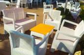Bílé židle s oranžovou tabulkou na ulici za občerstvení