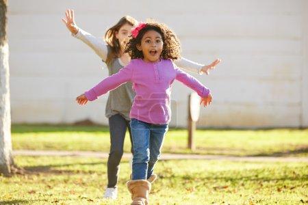 Multi ethnic kid girls playing running in park