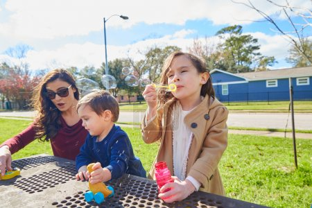 Mother daughter and son at park blowing bubbles