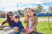 Matka, dcera a syn v parku vyfukuje bubliny