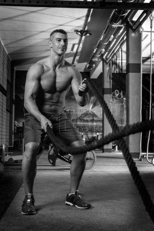 battling ropes man at gym workout exercise