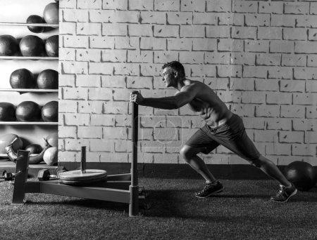 sled push man pushing weights workout
