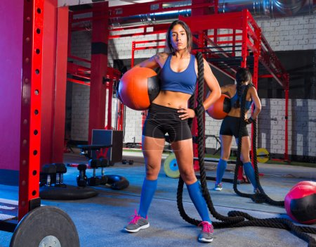 Photo pour Brunette gym woman with weighted ball and rope posing - image libre de droit