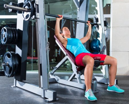Photo pour Barbell Incline Bench Press woman in multipower Smith machine workout at gym - image libre de droit