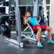 Barbell Incline Bench Press woman in multipower Smith machine workout at gym