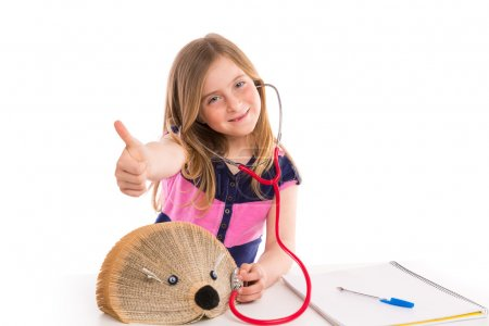 Foto de Blond kid girl pretending be a doctor with hedgehog book on white background - Imagen libre de derechos