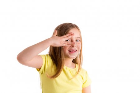 Foto de Blond indented kid girl hiding eyes with fingers gesture on white background - Imagen libre de derechos