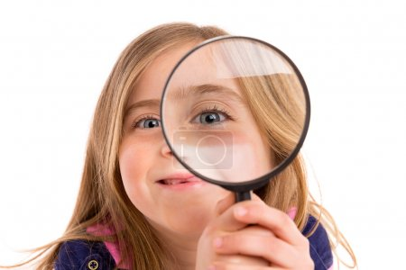 Foto de Blond indented girl with eye in magnifying glass funny expression on white background - Imagen libre de derechos