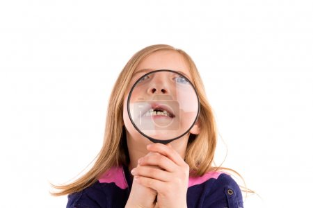 Foto de Blond indented girl with teeth in magnifying glass funny expression on white background - Imagen libre de derechos