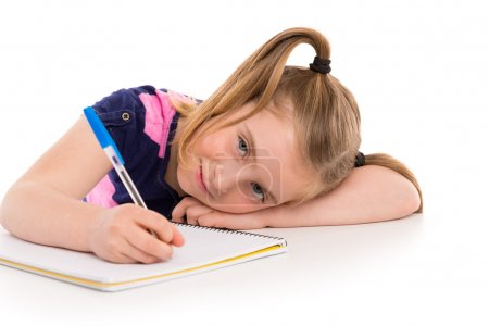 Foto de Blond kid indented girl student with spiral notebook in pupil desk - Imagen libre de derechos