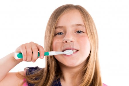 Foto de Blond kid indented girl cleaning teeth toothbrush on white background - Imagen libre de derechos