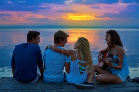 Friends group playing guitar in sunset pier at dusk