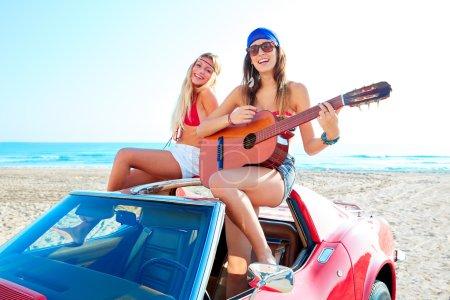 Photo pour Filles avoir plaisir à jouer de la guitare sur la plage th avec une voiture convertible - image libre de droit
