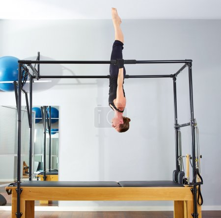 Pilates woman in cadillac acrobatic upside down