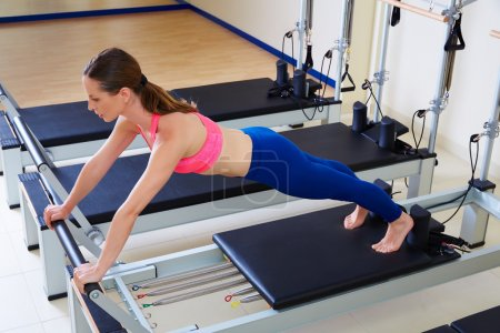 Pilates reformer woman long stretch exercise