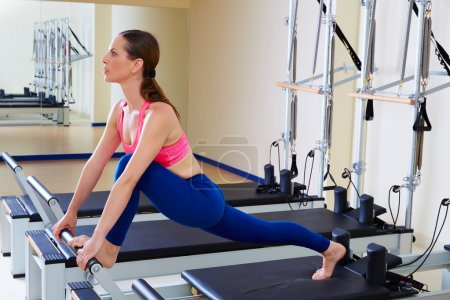Pilates reformer woman front split exercise