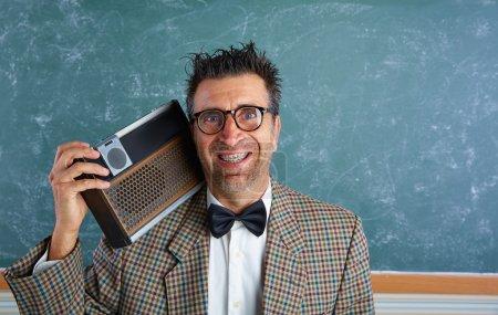 Photo pour Homme stupide professeur rétro nerd avec bretelles et radio vintage et expression folle - image libre de droit