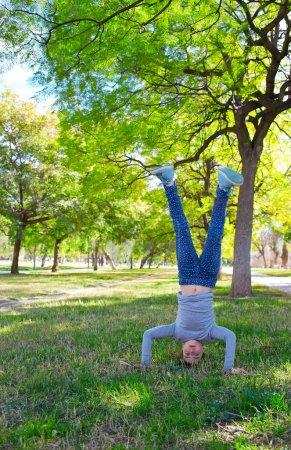 Kid girl handstands upside down in the park