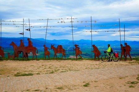 Foto de La forma del top del Alto del perdón de Saint James con la escultura de acero de peregrinos en Navarra con biker - Imagen libre de derechos