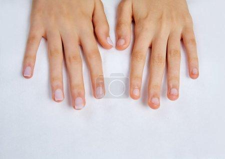 Photo pour Mains de femme avec des ongles avant le traitement sur une serviette blanche dans le salon - image libre de droit