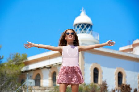 Blond girl open hands in Mediterranean Lighthouse
