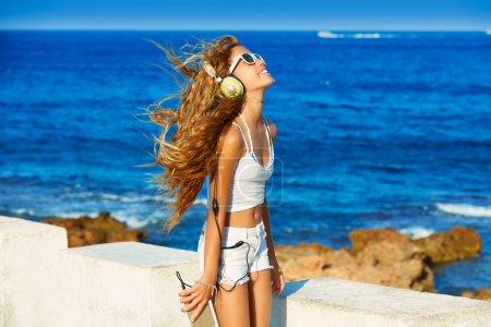 Photo pour Gamin blond teen girl audition casque musique sur smartphone dans une plage - image libre de droit