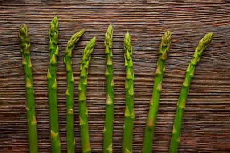 Photo pour Légumes crus d'asperges en rangée sur fond de bois vieilli - image libre de droit