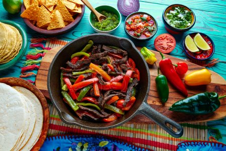 Beef fajitas in a pan sauces chili and sides Mexican