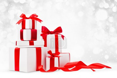 Christmas gifts with red ribbons on light backgrou...