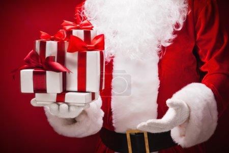 Foto de Santa Claus con regalos sobre fondo rojo - Imagen libre de derechos