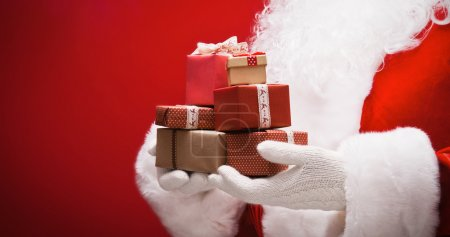 Photo for Santa Claus with gifts on red background - Royalty Free Image