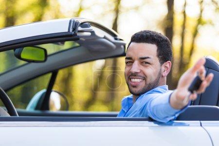Young black latin american driver holding car keys driving his n