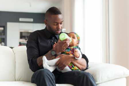 Young african american father giving milk to  her baby girl in a