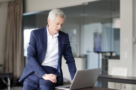 Senior businessman working on his laptop