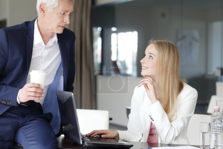 Sales woman with businessman working at office.