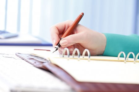 Businesswoman writing to her diary