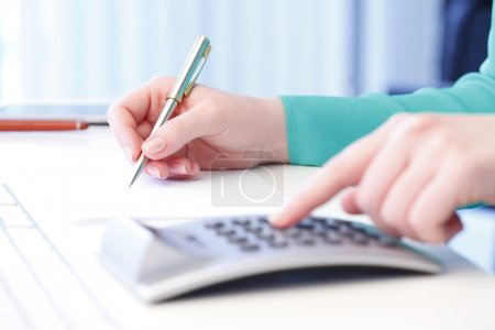 Photo pour Close-up of female accountant making calculations while sitting at desk in office. Businesswoman working on financial plan - image libre de droit