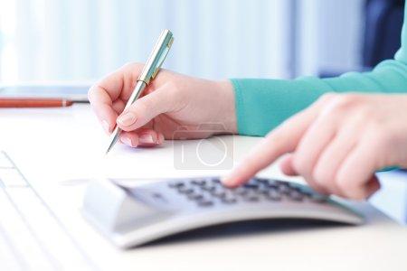 Photo pour Plan rapproché de comptable féminin faisant des calculs tout en s'asseyant au bureau dans le bureau. Femme d'affaires travaillant sur le plan financier - image libre de droit