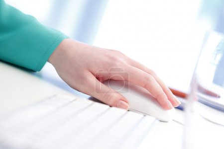 Woman's hand touching computer mouse