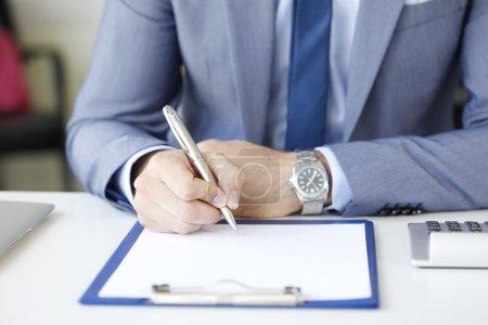 Photo pour Portrait d'homme d'affaires tenant crayon dans sa main et la signature du contrat à la réunion d'affaires. - image libre de droit