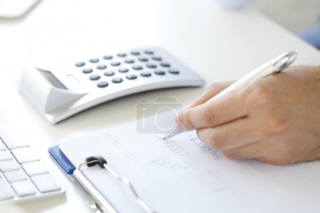 Photo for Close-up of investment advisor calculating expenses while sitting at office in front of computer. - Royalty Free Image