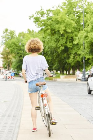 Photo for Rear view shot of a young woman riding on bicycle in the city. - Royalty Free Image