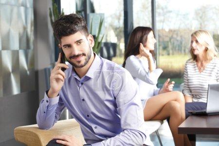 Photo pour Verticale de jeune homme d'affaires parlant à son mobile tout en s'asseyant à la réunion avec l'équipe d'affaires sur le fond - image libre de droit