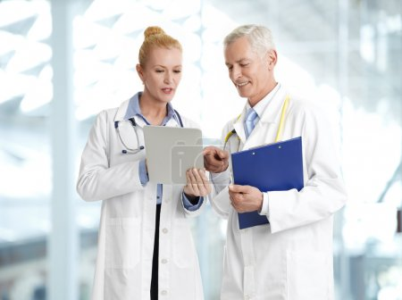 Doctors with tablet and clipboard
